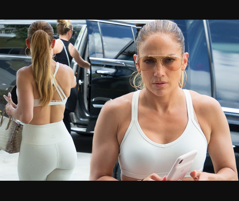 Jennifer Lopez showcases her famous backside in skintight white leggings and a sports bra