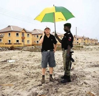 Viral photo of a Nigerian Mopol holding up an umbrella for his Chinese boss